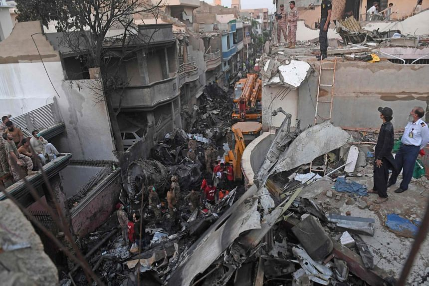 Security personnel search for victims in the wreckage of a Pakistan International Airlines aircraft after it crashed in a residential area in Karachi on May 22, 2020.