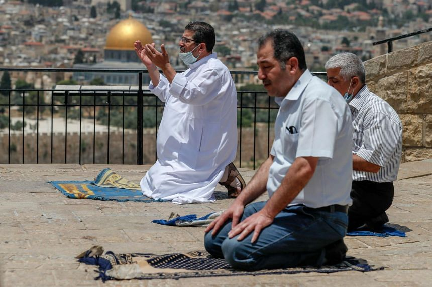 Palestinian men perform the last Friday prayer of the Muslim holy month of Ramadan at the Mount of Olives on May 22, 2020.
