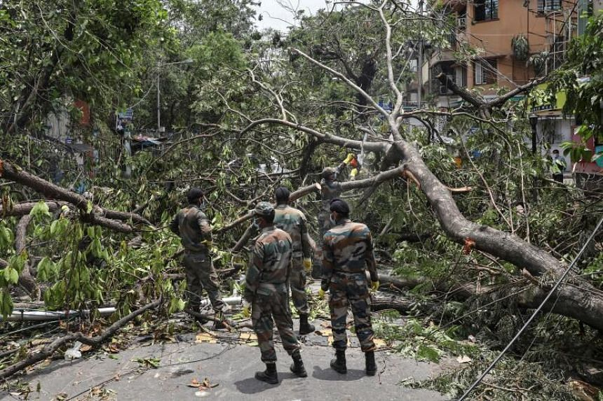 Indian Army soldiers cut trees to clear the roads in Kolkata, India, on May 24, 2020.