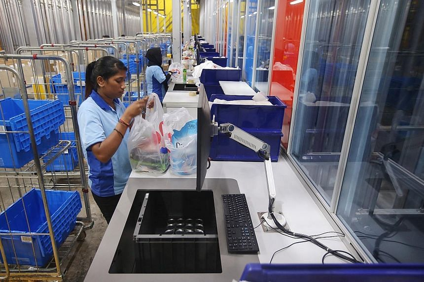 Above: A 2018 file photo showing packers at the FairPrice Hub distribution centre bagging items for online orders. Delivery slots were fully booked on many supermarkets' e-stores last month. ST FILE PHOTO Left: Deliveroo saw a 20 per cent increase in