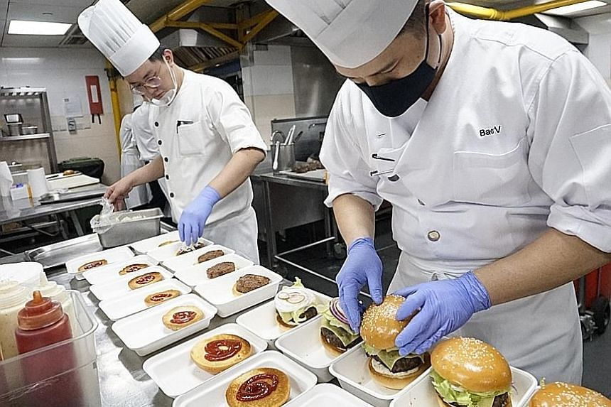 Grand Hyatt Singapore chefs preparing free burgers for F&B employees as part of the Together In Spirits campaign. EuroCham reimburses eateries $20 a meal to cover preparation and delivery costs.