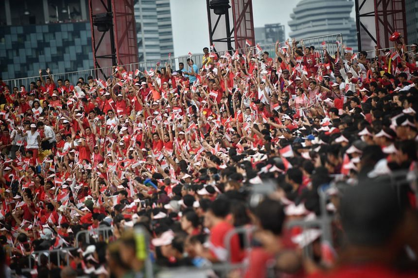 Spectators wave their flags as they join in the celebrations at the National Day Parade, on Aug 9, 2019.