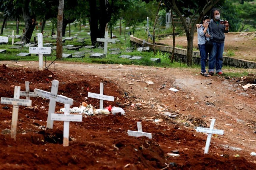 A photo from April 3, 2020, shows relatives of coronavirus victims standing next to graves in Jakarta.