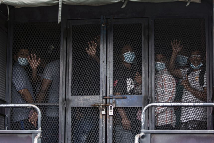 Migrant workers are transferred to a detention center after a raid in Petaling Jaya, Malaysia, on May 20, 2020.