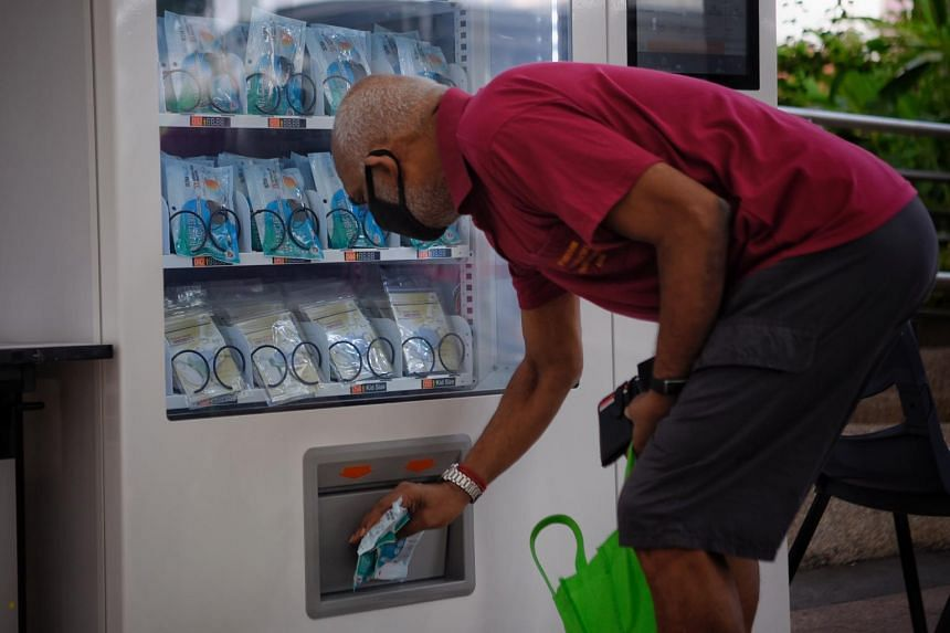 An elderly man collects his reusable mask from a vending machine at Bishan Community Club, on May 26, 2020.
