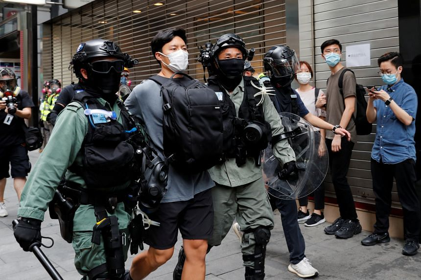 Riot police officers detain a demonstrator during a protest in Hong Kong on May 27, 2020.