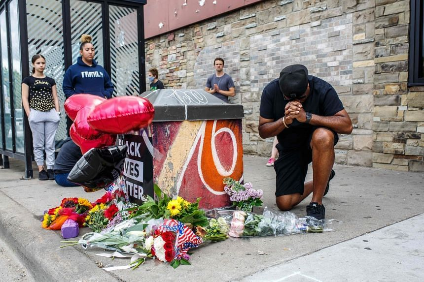 A protester prays in front of the memorial of George Floyd who died in custody in Minneapolis on May 26, 2020.