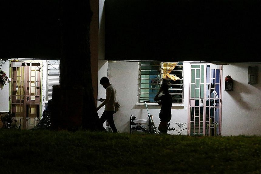 A Straits Times journalist at a block in Boon Lay being led by a man (left) to a flat where a Thai card game was to be played. Two men had watched to ensure the journalist was alone before they brought her up to the unit. She left before the session