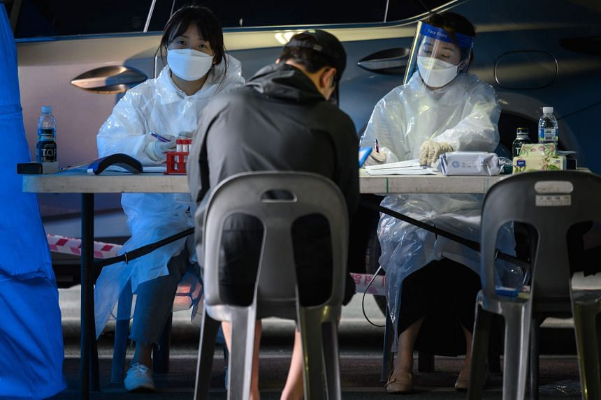 Healthcare workers attend to visitors to a temporary Covid-19 testing centre in Bucheon, south of Seoul, on May 27, 2020.