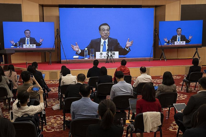 Chinese Premier Li Keqiang seen speaking on screens during his remote video-streamed press conference marking the end of the third plenary session of the 13th National People's Congress in Beijing yesterday. PHOTO: EPA-EFE