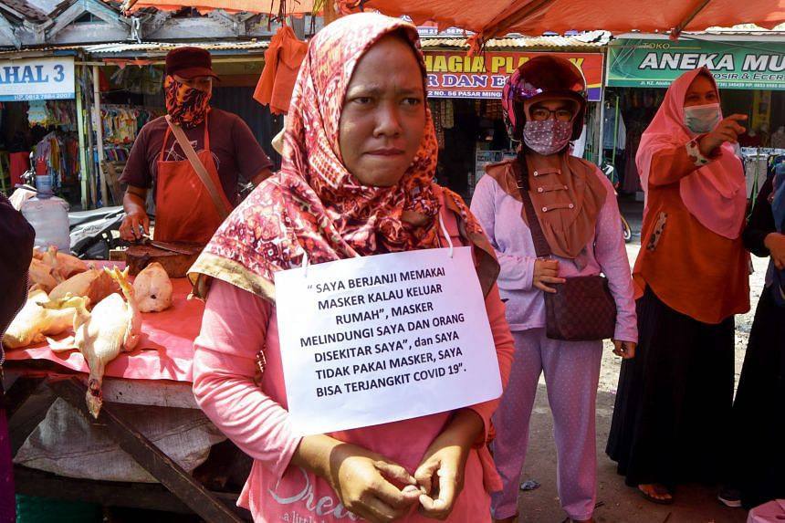 """A violator wearing a sign reading """"I promise to wear face mask"""" in Bengkulu, Indonesia."""