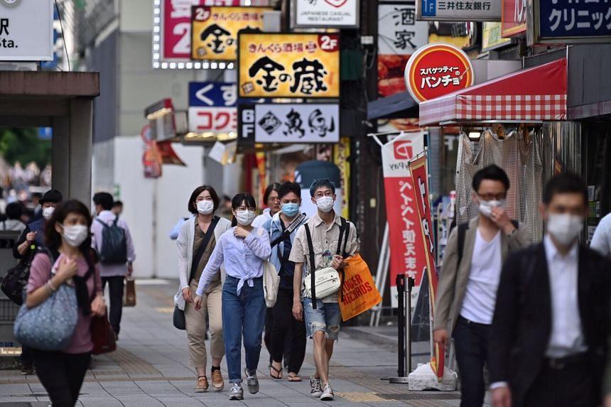 People walk in a street in Tokyo's Akihabara area on May 27, 2020.