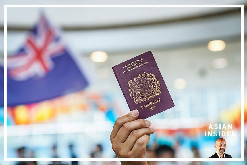 A demonstrator shows a British National (Overseas) passport as another waves a colonial-era Hong Kong flag during a lunchtime protest at the International Finance Center (IFC) shopping mall in Hong Kong, China, on Friday, May 29, 2020.