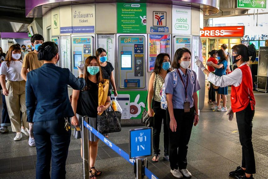 Employees check the temperature of passengers at a commuter train station in Bangkok, on May 25, 2020.