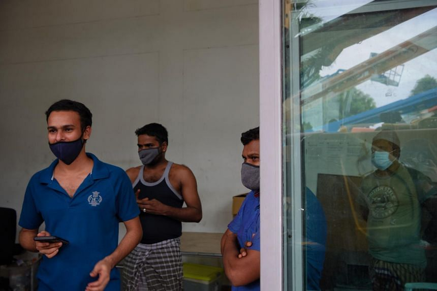 Migrant workers look out from a factory-converted dormitory before collecting supplies sent to them by NGO Alliance of Guest Workers Outreach at Tech Park Crescent in Tuas on May 27, 2020.