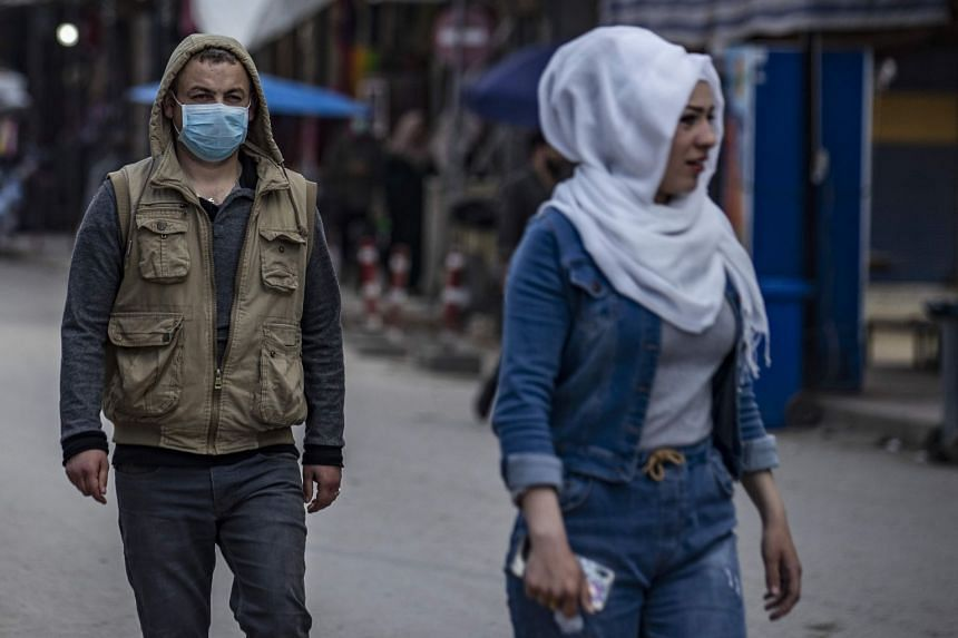 A man wearing a protective mask walks along a market street in Qamishli in Syria's northeastern Hasakah province on March 22, 2020.