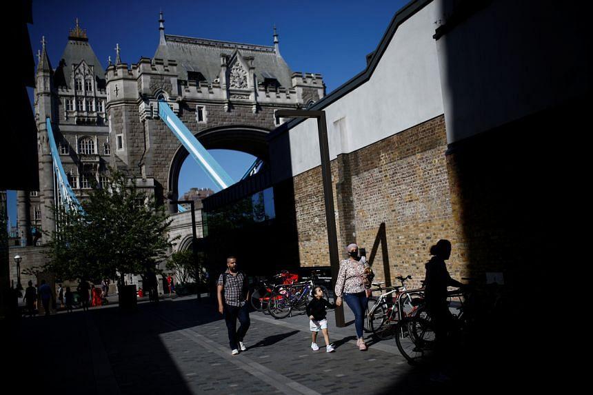 People walk near Tower Bridge in London, on May 28, 2020.