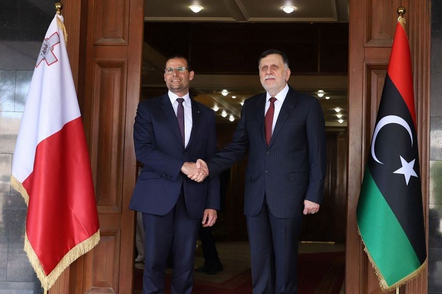 Malta's Prime Minister Robert Abela (left) is greeted by Prime Minister of Libya's UN-recognised Government of National Accord Fayez al-Sarraj on May 28, 2020.