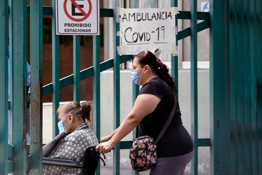 A woman pushes a relative's wheelchair as they enter a general hospital in Mexico City on May 29, 2020.