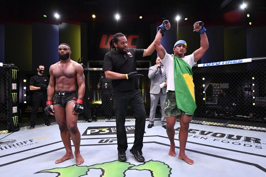 Gilbert Burns (blue gloves) reacts after his victory over Tyron Woodley in Las Vegas on May 30, 2020.