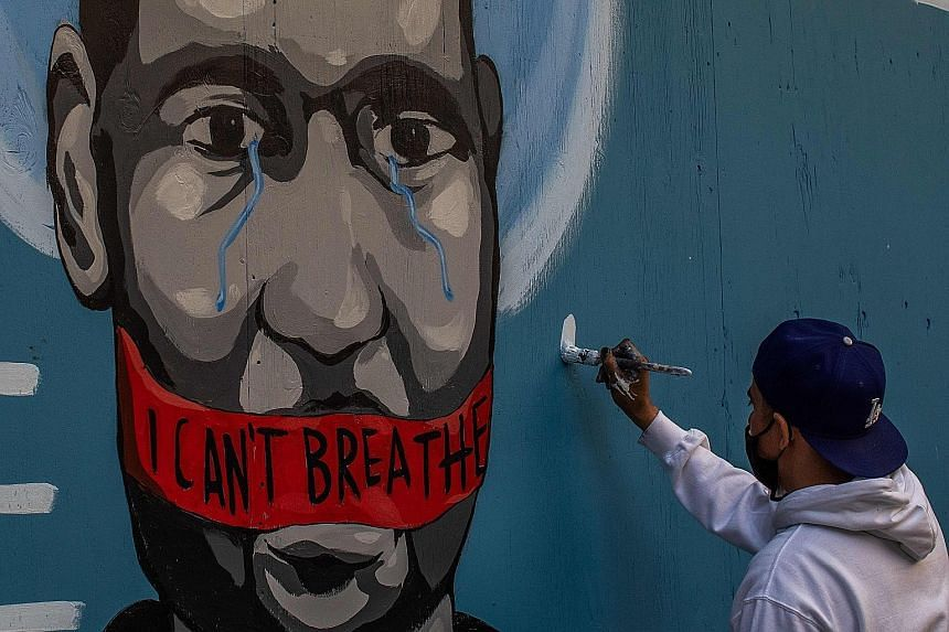 An artist named Celos painting a mural in Los Angeles last Saturday in protest against the death of Mr George Floyd.
