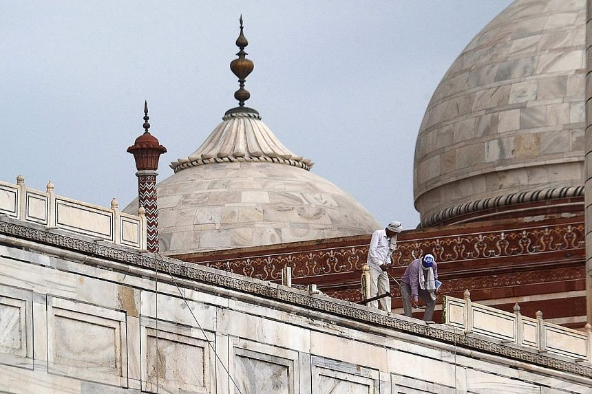 Workers assessing the damage at the Taj Mahal after parts of the complex were damaged in a heavy storm last Friday night. PHOTO: AGENCE FRANCE-PRESSE
