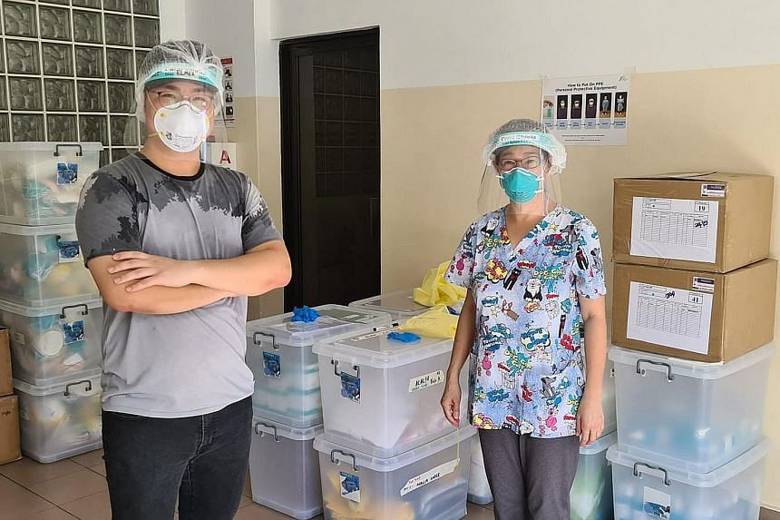 """Volunteer """"swabber"""" Elmer Chan (left), who graduated last month with a diploma in aviation management and services, with Dr Lim Lii, who carries out swab tests and trains would-be """"swabbers""""."""