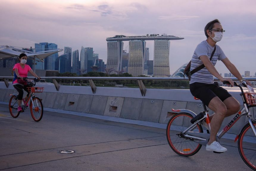 People wearing masks cycle at Gardens By The Bay East on May 30, 2020.