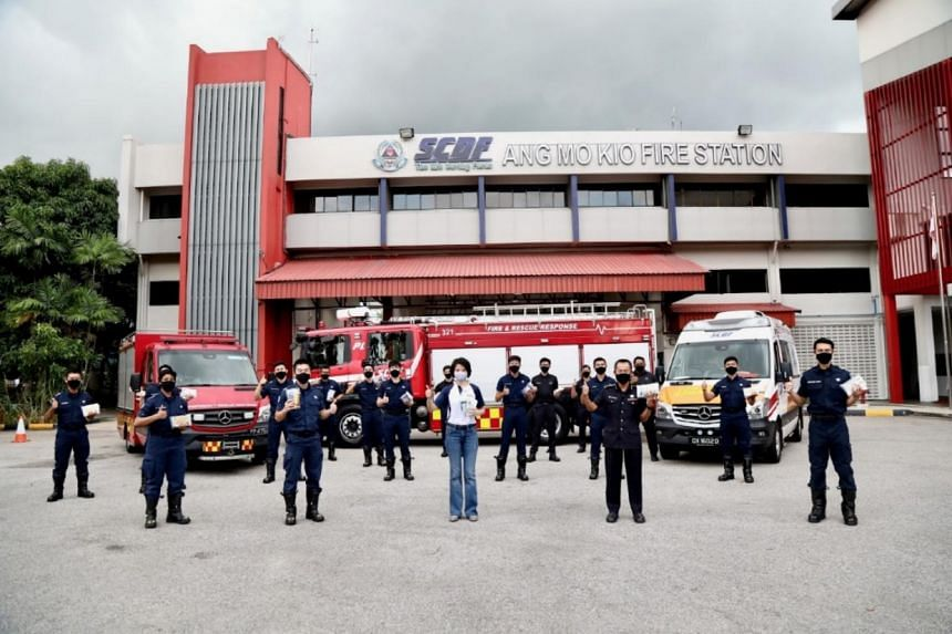 Senior Parliamentary Secretary of Home Affairs Sun Xueling and Singapore Civil Defence Force officers from Ang Mo Kio Fire Station with the care packs.