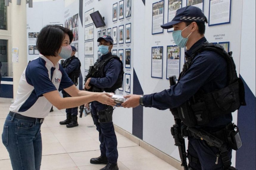 Senior Parliamentary Secretary of Home Affairs Sun Xueling presents a care pack to a Singapore Police Force officer.