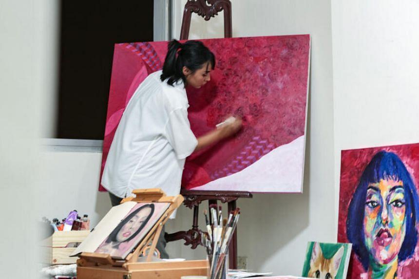 Visual artist Lis Tamara Ahmad Razib painting a work at her home studio in September 2019.