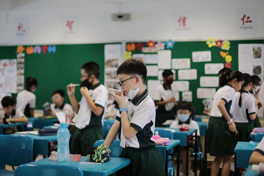 Xingnan Primary School pupils take their temperature in class on June 2, 2020.