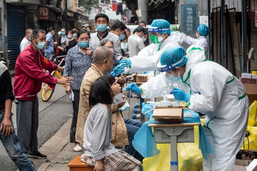 Medical workers take swab samples from residents in a street in Wuhan, on May 15, 2020.