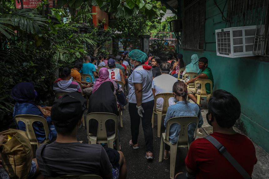 A health worker (centre) assists people lining up for a rapid test in Manila on May 24, 2020.