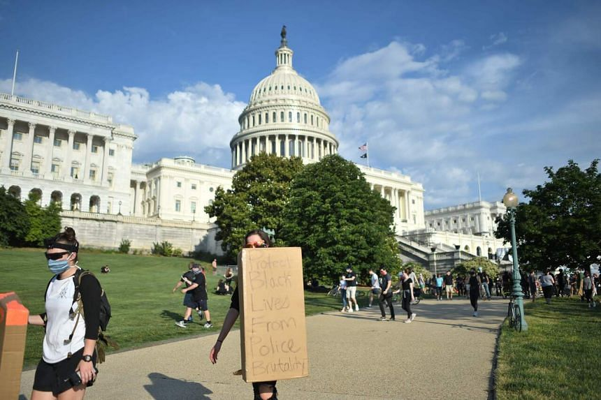 Demonstrators holding signs during a protest in front of the United States Capitol in Washington, DC on June 2, 2020.