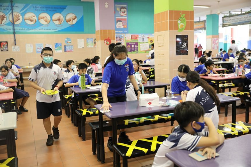 Primary 6 pupil Japhanie Tan of Jing Shan Primary School wiping down the table in the canteen after finishing her lunch yesterday. Despite restrictions such as having to wear face masks throughout the day, not talking to friends without masks on and
