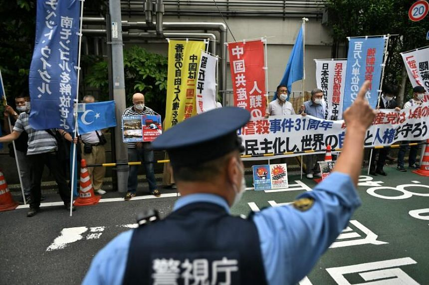 A policeman guides the traffic as a group of pro-democracy activists hold a silent prayer before a protest at the Chinese embassy in Tokyo on June 4, 2020.