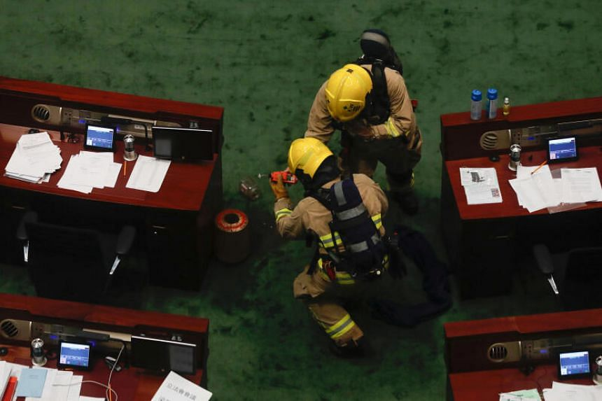 Hong Kong firefighters checking the chamber of the Legislative Council after pro-democracy lawmakers hurled objects during third reading on the controversial national anthem Bill on June 4, 2020.