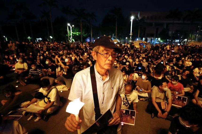 Lam Wing Kee, a former Hong Kong publisher holds a candle as he joins a vigil of the Tiananmen Massacre, in Taipei, on June 4, 2020.