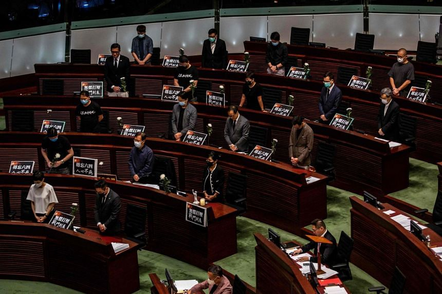 Pro-democracy legislator stand in silence before walking out of the chamber in Hong Kong, on June 4, 2020.