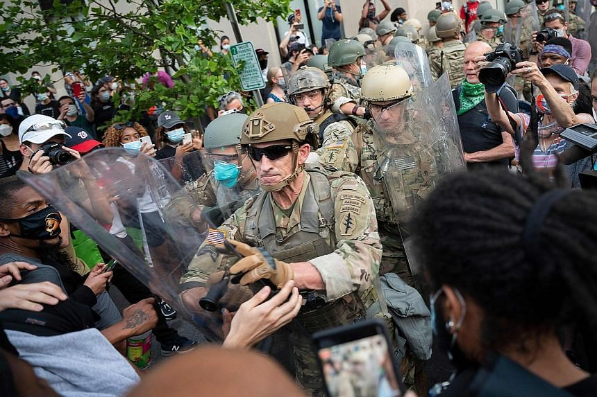 Protesters scuffling with US Army soldiers near the White House in Washington, DC on Wednesday. The unrest, however, was far less destructive on Tuesday and Wednesday than during the previous few days. Above: A crowd protesting in San Francisco, Cali