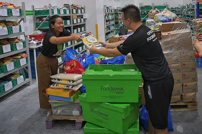 Ms Audrey Wong and Mr Jameson Chow of The Food Bank Singapore sorting out donated food last December. The new virtual food banking app will allow donors to share the type and quantity of food they have in real time, which food support organisations c