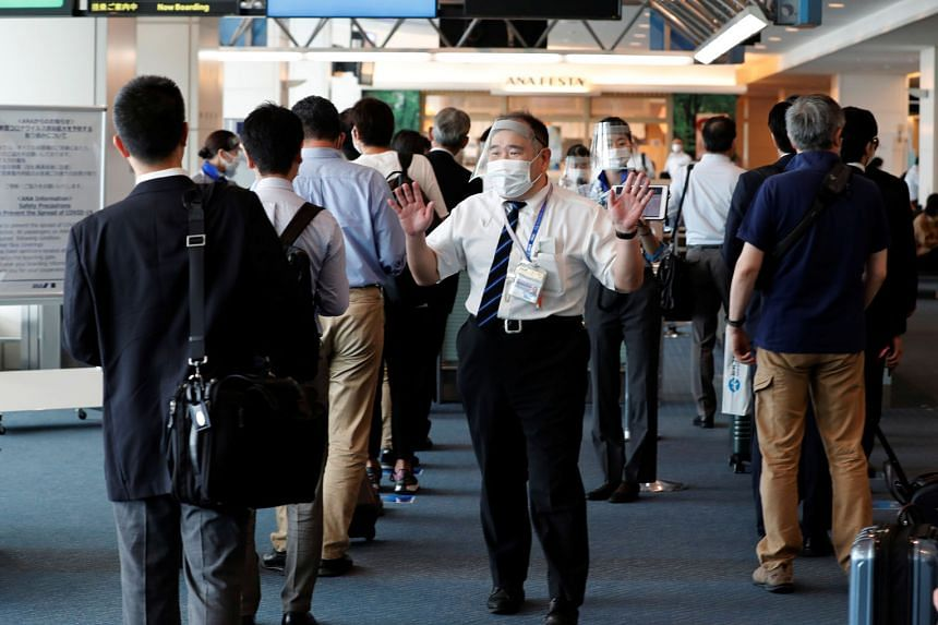 An All Nippon Airways staff member reminding passengers to keep to social distancing measures at Haneda Airport yesterday. Japanese nationals, while discouraged from travelling, are permitted to return to Japan.