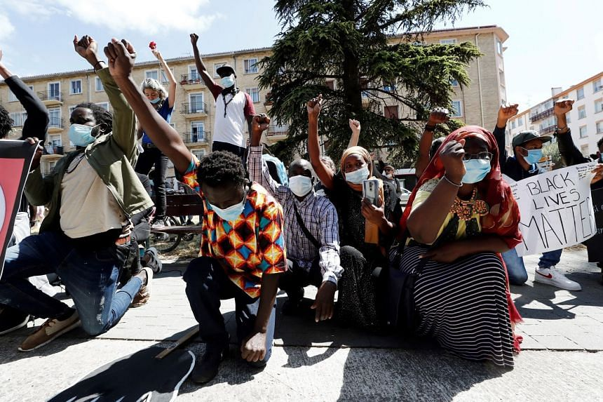 People raise their fists during a protest against the death of George Floyd in Pamplona, Navarra, Spain.