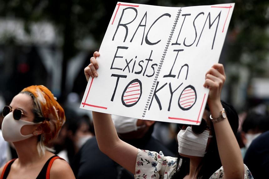 A demonstrator holds a placard during a Tokyo protest over the alleged police abuse of a Turkish man.