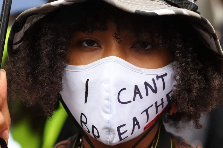 """A protester wears a face mask reading """"I can't breathe"""" at a rally in Germany over the death of George Floyd."""