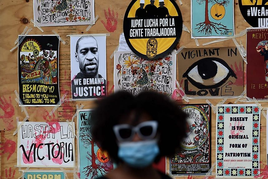 A demonstrator walks past a mural for George Floyd during a protest near the White House on June 4, 2020.