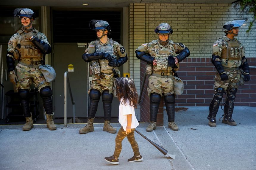 A child carrying a small broom walks past a line of National Guard members deployed in Washington amid protests, June 1, 2020.