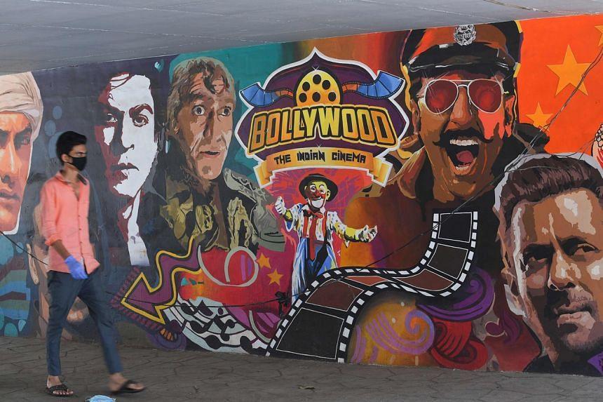 A man walks past a wall mural of Bollywood actors in Mumbai. on May 8, 2020.