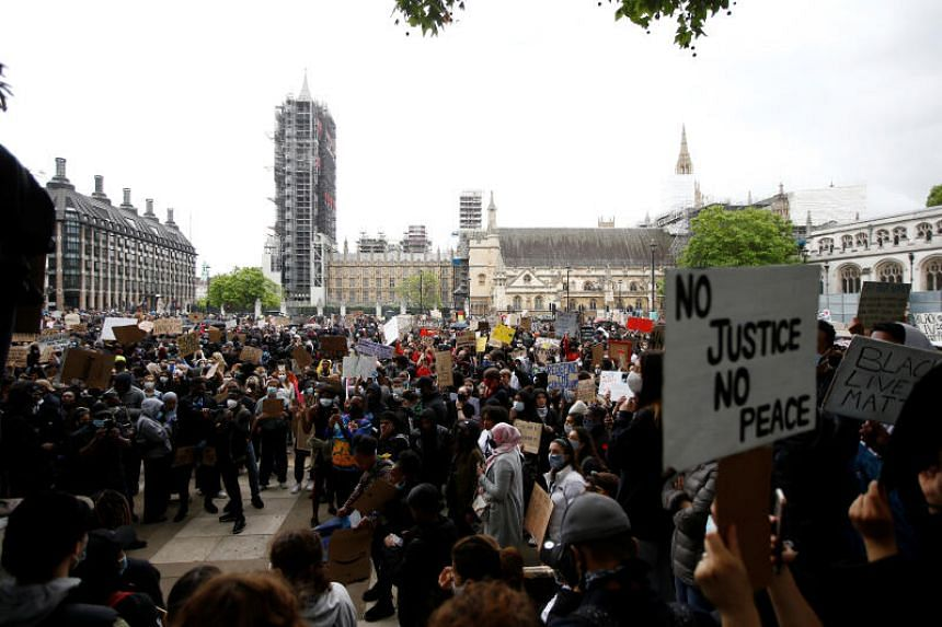 Protesters hold up signs in Parliament Square during a Black Lives Matter protest in London, on June 7, 2020.
